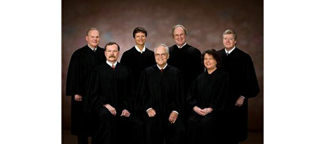Kansas Supreme Court Chief Justice Robert E. Davis has retired from his seat. He is pictured in this official photograph with the entire court. Seated (from left) are Justices Lawton R. Nuss, Davis and Marla J. Luckert. Standing (from left) are Justices Lee A. Johnson, Carol A. Beier, Eric S. Rosen and Dan Biles. With Davis' retirement, Nuss becomes chief justice.