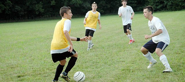 Baldwin High School junior Louis Joslyn, left, maintains possession of a ball during a drill last week. The Bulldogs have been working all summer on improving fundamentals.