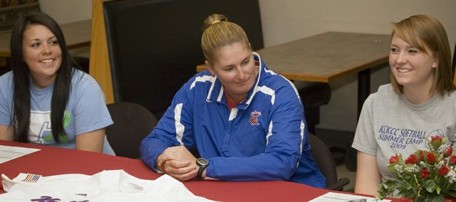 Angela Jacobs, left, and Nikki Pennington, right, smile at a signing ceremony with Kansas City Kansas Community College softball coach Kacy Tillery. Jacobs and Pennington, Tonganoxie High graduates, are looking forward to remaining teammates at KCKCC.