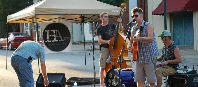 Members of the band the F Holes perform during the inaugural First Thursday in the 600 block of Fourth Street in downtown Tonganoxie. Businesses in the downtown block are offering discounts on the first Thursday of each month and are working to line up entertainment for the special Thursdays, also.