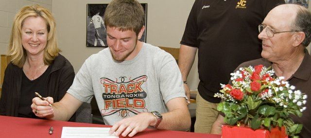 Stephen Wilson signs his letter of intent to throw for the track team at Johnson County Community College as his parents, Betty and Larry, watch. Wilson threw the discus his senior year at Tonganoxie High.