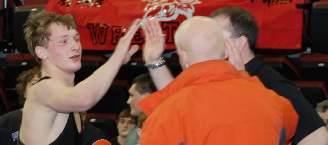 Bonner Springs freshman 140-pounder Aaron Puckett is congratulated by his coaches after advancing to the medal rounds Saturday at the Class 5A state tournament. Puckett finished fourth.