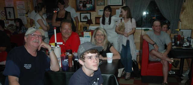 Bob Caviar, far left, owner of Papa Bob's BBQ in Bonner Springs, watches the Man v. Food episode featuring his restaurant Wednesday night with a crowd of customers and supporters.