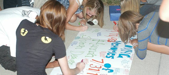 Friends write favorite memories and sign a poster for the family of Hannah Deaver. Family and friends had a vigil Aug. 4 in memory of the 17-year-old Mill Valley High School student who died July 31.