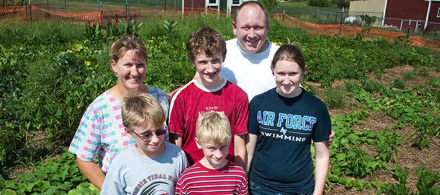 Janet and Dave Falk stand in their family garden behind their children, from left, Luke, 11, David, 14, Alex, 9, front, and Lacie, 17.