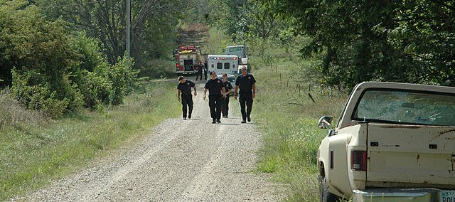 A Lawrence-Douglas County Fire and Medical crew heads back to their fire engine after helping free a man that was injured in a trench accident Monday afternoon west of Baldwin City. A helicopter ambulance was dispatched to the area. More details as they become available.