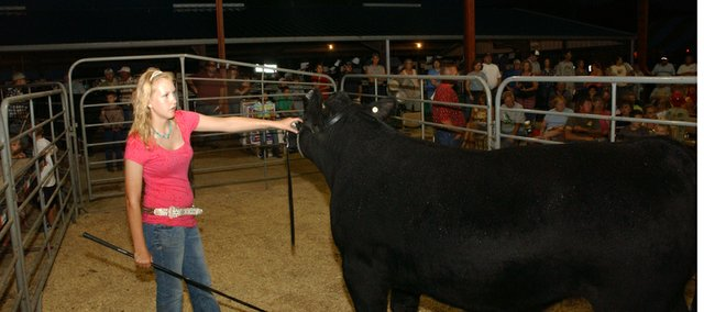 Jody Baragary leads her grand champion market steer in the auction pit Friday at the Leavenworth County Fair. The steer fetched $3,300 as bidders rewarded Baragary and other 4-H'ers for work on their projects.