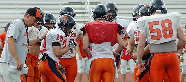Baker University football coach Mike Grossner, left, talks to his offensive team during their huddle at practice Tuesday afternoon.