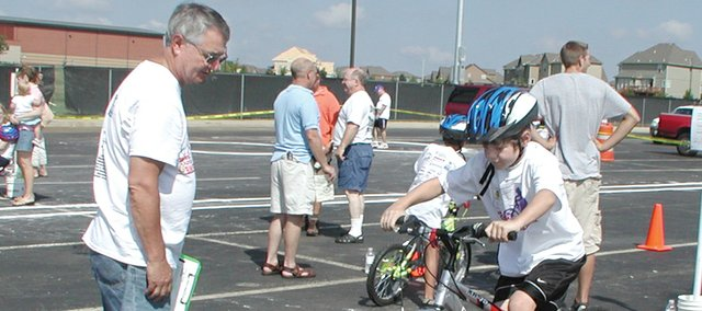 Austin George, 9, of Olathe, comes to a quick stop at the second station of the Shawnee Rotary Bike Rodeo in 2007. At left is Leon Logan, Rotary Club volunteer. This year's bike rodeo begins at 9 a.m. Saturday at Mill Valley High School.