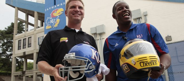 NASCAR driver Clint Bowyer, an Emporia native, exchanges helmets with Kansas football coach Turner Gill during a tour of the Anderson Family Football Complex on Tuesday.