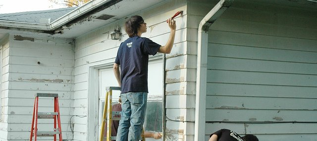 Baker University students paint a home as part of the Neighbors Helping Neighbors project in an area community.