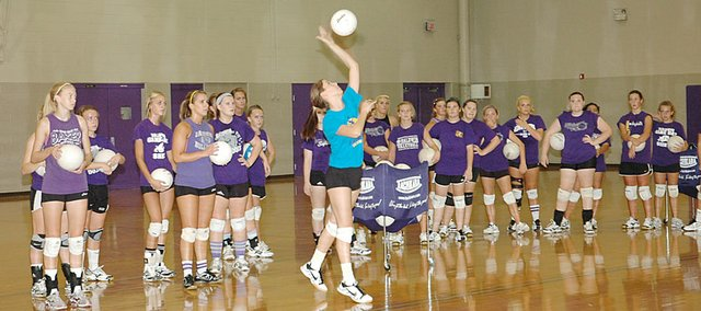 Baldwin High School senior Ramie Burkhart, center, practices her serves while the rest of the Bulldogs watch before taking their turn Tuesday afternoon.