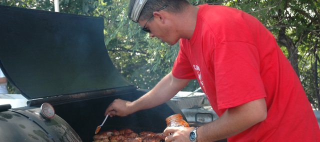 John Frank, a member of the KC Smokin' Boys team, spread sauce on his chicken selection for the Smokin' on Oak barbecue competition during Tiblow Days.
