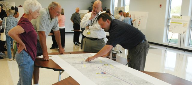 Ann Davis and her husband, Rick, both on the left-hand side of the table, talk to engineers about the design plan for the new Kansas Highway 7/Interstate 70 interchange during a public meeting last Wednesday at the Bonner Springs High School cafeteria. Construction is expected to begin on phase two in 2012.