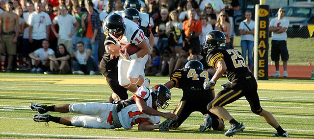 Baker University freshman quarterback Jake Morse dives over one of his own players Saturday during the first half. Baker lost the game 24-14 to Ottawa University.