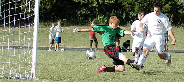 Baldwin High School soccer junior Caleb Michels, right, kicks the ball past the Tonganoxie goalkeeper Friday afternoon. His goal helped the Bulldogs win 1-0. On Tuesday, the Bulldogs beat Paola 1-0 to begin the season 2-0.