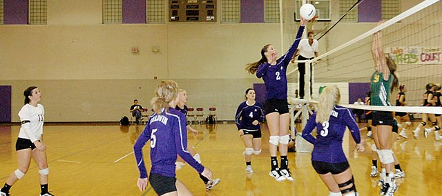 Baldwin High School senior Ramie Burkhart, center, tips a ball over the net Tuesday night against Basehor-Linwood. The Bulldogs won the match, 22-25, 25-23 and 25-21.