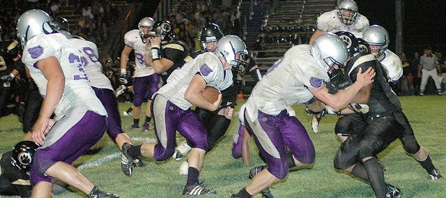 Baldwin High School senior Ryan Rogers, center, follows his blockers during a run up the middle of the Paola defense. Rogers scored one rushing touchdown and one receiving during the Bulldogs' 32-14 victory.