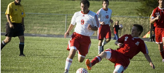 Joseph Parino avoids an Atchison defender as he leads a Tonganoxie High attack Tuesday afternoon. The Chieftains lost their home opener to AHS, 2-1, in double overtime.