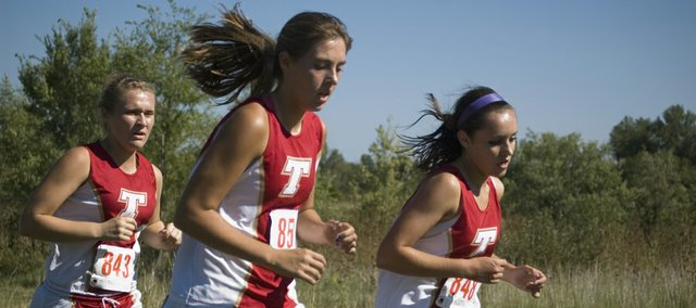 Tonganoxie High cross country runners Parker Osborne, Emma Stilgenbauer and Amanda Shepley run in the girls 4K Friday. The girls and boys teams lost in home duals against Lansing.