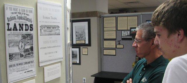 Chris Garcia, left, and his son T.J. examine advertisements that railroad companies used to entice Russian-German farmers to purchase land in Kansas. Chris and Janice Garcia sponsored this month's exhibit at the Basehor Historical Museum about the Russian-German immigrants' experience.