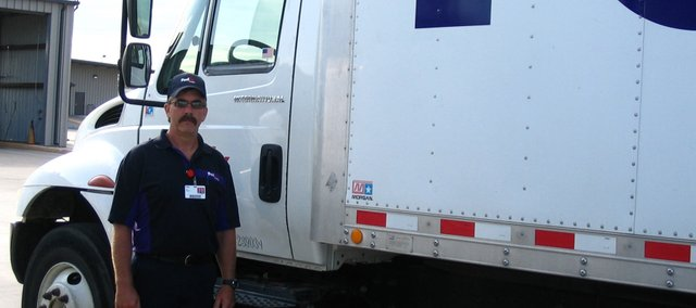 Jay Miller, Bonner Springs resident and driver with FedEx Freight, stands next to the straight truck he practiced with in preparation for the Kansas Truck Driving and National Truck Driving championships. Miller, who has participated in the Kansas competition for the past 10 years, got to go on to the national competition for the first time this year.