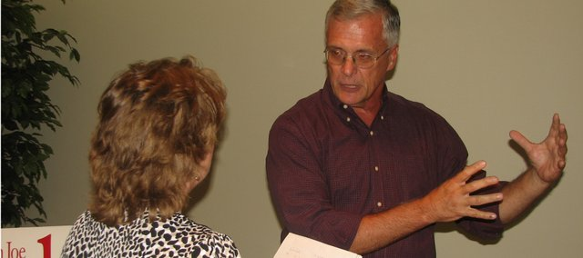 Joe Novak (right), Democratic candidate for the Kansas House of Representative, answers questions from Sabrina Valenta of Leavenworth County at the Basehor Community Librarys candidate open house Thursday evening. 