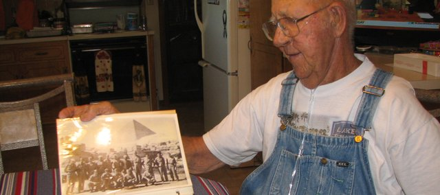 Harry Kelley, of Basehor, flips through a scrapbook, displaying a photo of him and other World War II prisoners of war in Cairo, Egypt, after being freed at the end of the war. Kelley said one other person in the photo was still alive. Kelley will celebrate his 90th birthday at 3 p.m. Saturday at the Basehor VFW post.