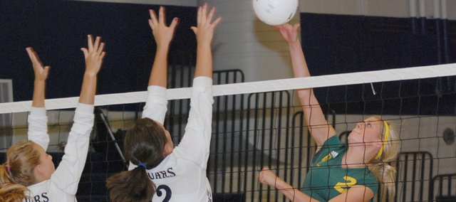 Basehor-Linwood junior Cara McCarty tips the ball over the block of Mill Valley's Dani Niemann (4) and Madison Acree (12).