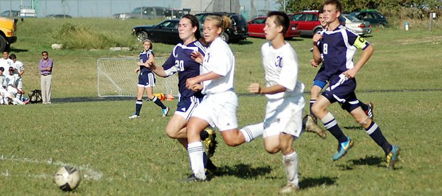 Baldwin High School sophomore Jessie Katzer and junior Caleb Michels race toward a ball Tuesday afternoon. Michels only needed one touch on the ball as he scored the Bulldogs' second goal of the contest. Michels scored three goals as Baldwin beat Eudora 4-2.