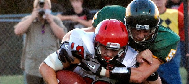 Lansing High quarterback Tyler Terron is wrapped up by Basehor-Linwood's Ben Johnson. BLHS beat LHS, 26-7.