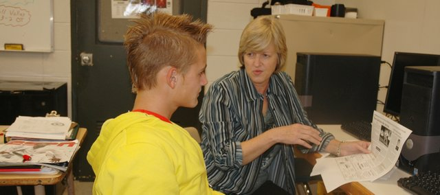 Jill Holder, right, Bonner Springs High School journalism teacher, helps Austin Epp, BSHS senior, with a journalism assignment. The state recently announced it would be cutting funding for high school journalism programs.
