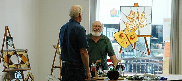 David Anderson, right, of Globe Art Glass Studio talks to a visitor Friday night at the Baldwin Community Arts Council's Art Walk finale. Anderson donated the large piece hanging in the window to the BCAC.
