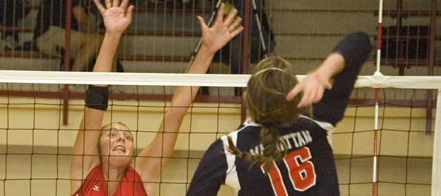 Molly O'Hagan throws her arms up in preparation as Manhattan High's Mari Jo Massanet goes for a spike in the Tonganoxie Invitational semifinals on Saturday. Tonganoxie lost to MHS and finished fourth at the tournament.