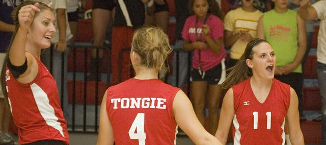 Haley Smith, right, celebrates with Molly O'Hagan and Sagan Scates after Tonganoxie High defeated Mill Valley at its home triangular on Tuesday.