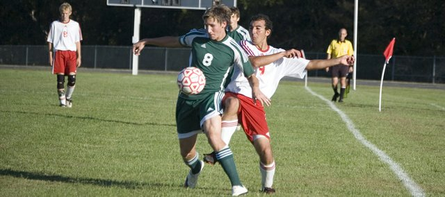 Patrick Rutherford of Basehor-Linwood High holds off Tonganoxie's Joseph Parrino in the second half of the Bobcats' 3-2 victory at THS on Wednesday. Rutherford had a goal and an assist for BLHS.