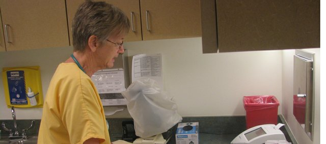 Nurse Stephanie Spacek flips through files in a lab room at St. Vincent Clinic at 818 N. Seventh St. in Leavenworth. The clinic treats uninsured Leavenworth County residents who meet income qualifications.