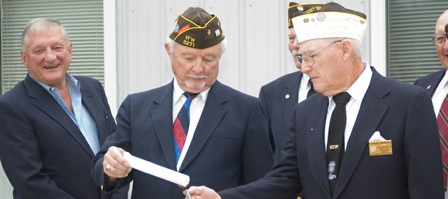 Tonganoxie VFWPost 9271 Post Commander Galen Freeman, middle, and Quartermaster Richard Bronaugh, right, burn mortgage papers for an addition to the post home that now is paid off. At left is Bill New. The event put the finishing touches on a 25th anniversary celebration for the local post.