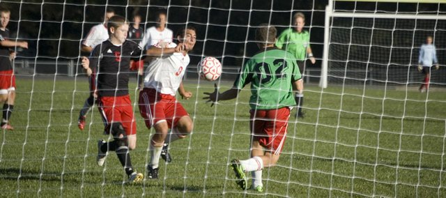 Tonganoxie High defender Joseph Parrino and goalkeeper Cody Martin try to keep a Lansing forward away from the ball on Monday. The Chieftains lost the home match, 3-0.