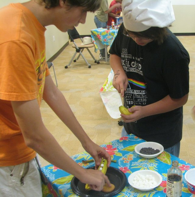 "Lee Maughmer (left) and Patrick Williamson, Basehor-Linwood High School sophomores, prepare marshmallow-stuffed ""Bananas on the Go"" at the Basehor Community Library's ""Teen Iron Chef"" event."