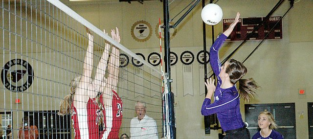Baldwin High School junior Madeline Brungardt spikes a ball over two Eudora defenders Tuesday night. BHS lost the match in three straight games.