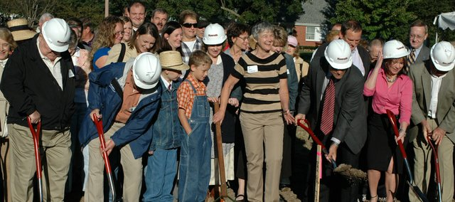 Museum director Gay Clemenson, center, laughs as city officials break ground for Shawnee Town's farmstead.