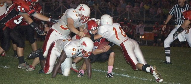 A group of Tonganoxie High defenders, led by Adam Thomas (10), take down Lansing quarterback Tyler Terron on Friday at LHS. The Chieftains lost, 42-24.