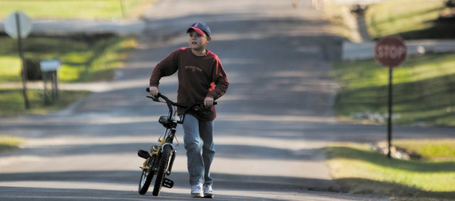 Ethan Folks, a Eudora 10-year-old with autism, walks his bike up to his home Wednesday. Ethan and his family will be participating in Walk Now for Autism Speaks on Saturday for the third time. The goal of the event is to raise awareness for autism and to raise funds for autism research.