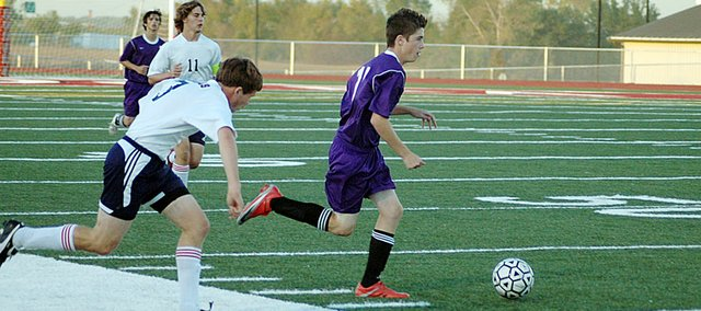 Baldwin High School freshman Duncan Murray dribbles past a Eudora defender last Thursday. The Bulldogs won the game 3-1 to sweep the Cardinals for the season.