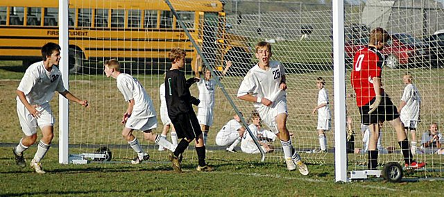 Baldwin High School junior Clint Chapman, center, celebrates after scoring the game-winning goal Tuesday. Baldwin beat rival De Soto, 3-2, on senior night in what was the last regular season game for the Bulldogs.