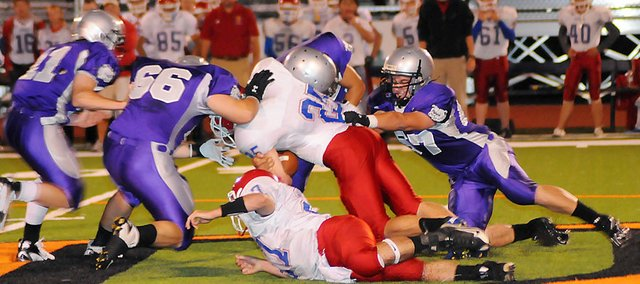 Four Baldwin High School football players smother a Santa Fe Trail running back Friday night at Liston Stadium. Baldwin crushed the Chargers, 53-14, to improve to 7-1 on the season and 2-0 in district play.