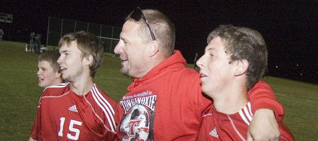 Tonganoxie High senior Quinten Olson, coach Brian Kroll and junior Cody Martin walk off the field with smiles on their faces after the Chieftains defeated Basehor-Linwood to win their second road playoff match in two nights.