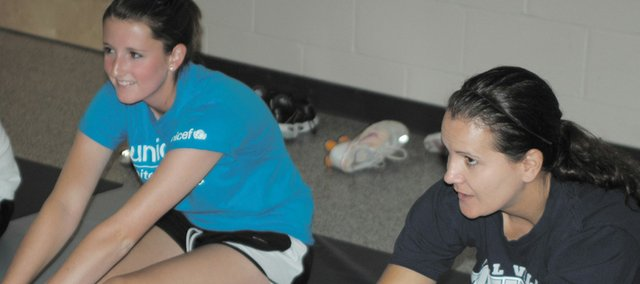 MVHS physical education teacher Amy McClure, right, stretches with Shannon McGraw during class. McClure was named the 2010 Outstanding School Health Educator by the American School Health Association.