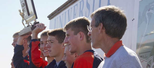 The Shawnee Mission Northwest boys cross country team hoists the 2010 Class 6A state championship trophy.
